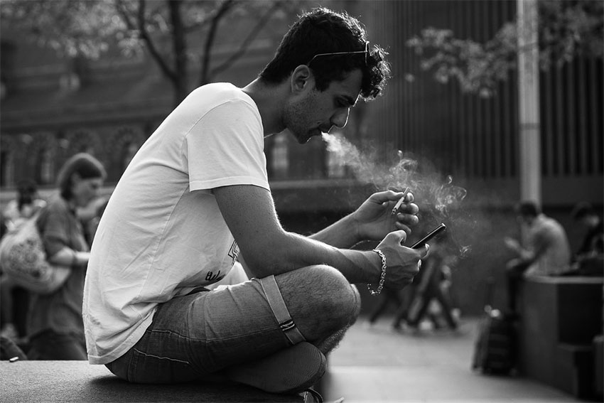 A man smoking cigarette and looking into the phone